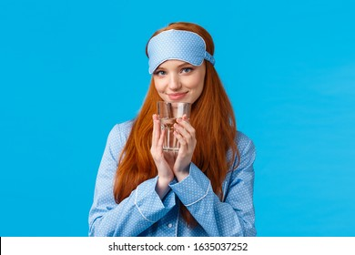 Silly and flirty, feminine redhead woman in cute nightwear and sleep mask, looking coquettish with pleased tender smile, drinking water, start day healthy and active, standing blue background