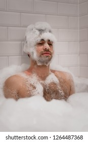 Silly, funny man looks at camera with neutral expression, covered in soap bubbles from a bubble bath in the tub