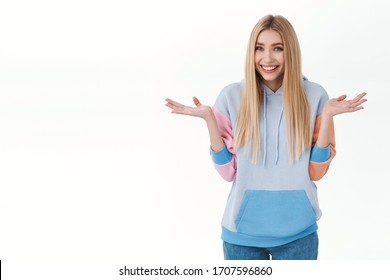 Silly giggling cute blonde girl in hoodie, shrugging and spread hands sideways, smiling as saying sorry, apologizing for cant help, being clueless and unaware, standing white background