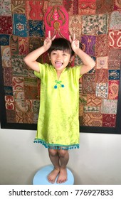 Silly girl in kaftan dress , standing in front of Indian tapestry.