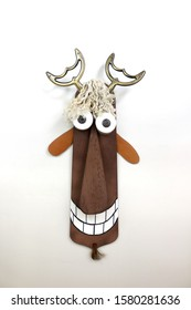 Silly grinning billy goat wall hanging made from found objects hanging on a white wall.