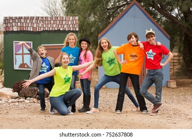 Silly group of friends at acting camp pose together in front of stage set