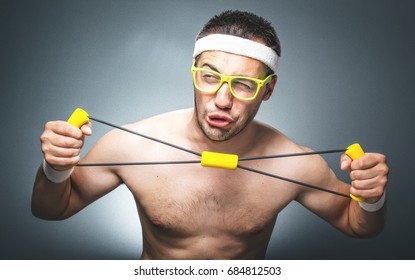 Silly man exercising over dark gray background. Nerd guy with eyeglasses holding expander. Close up of funny young man  doing aerobics. Studio shot
