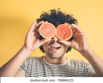 A silly young man is pretending to use two grapefruit halves as binoculars