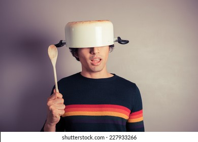 A silly young man is wearing a cooking pot on his had and is holding a wooden spoon