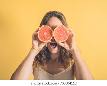 A silly young woman is pretending to use two grapefruit halves as binoculars