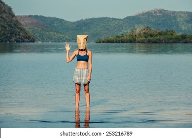 A silly young woman wearing a paper bag over her head is standing on a tropical beach and is waving