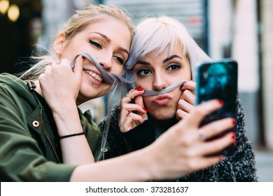 Silly Young women best friends taking a selfie