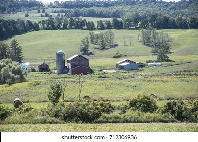 Silo and red barn surrounded by green fields and trees