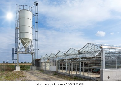 Silo at a sewage sludge drying plant with a greenhouse for solar sewage sludge drying