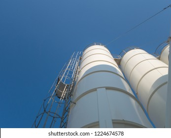 Silo, a tall cylindrical container for the storage of bulk granular products, a part of the concrete producing factory. Bottom view of the side stairs, close up