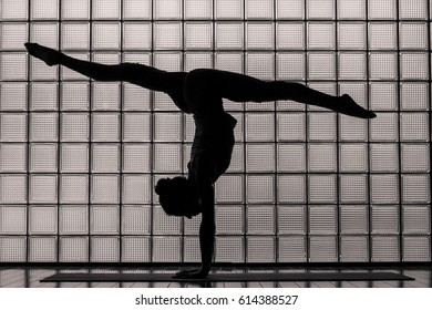 Silohuette of a beautiful  young woman practicing advance yoga indoors