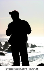 Silouette of a man standing at the edge of a cliff at Bodega Head, California.