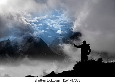 Silouette of a man stands out on a mountain panorama. The sky is threatening with many clouds and storm coming.