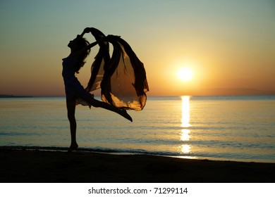 Silouette of the nifty woman dancing at the sea during sunset. Natural light and darkness. Artistic colors added