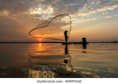 A siluate fisherman casting a nets into the water on during sunrise,Thailand