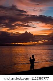 Silueta de mamá con bebé sobre cielo rojo del atardecer en playa Puntarenas, Pacífico de Costa Rica