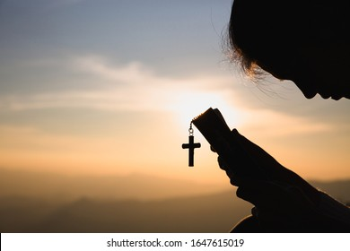 Siluette of Christian woman  holding a bible and wooden Christian cross necklace while praying to God.