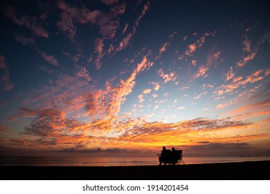The siluette of a couple sitting by the sea and admiring the amazing and colorful sunset