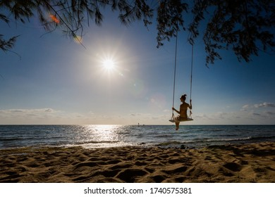 Siluette of woman on swing on tropical island Phu Quoc in Vietnam. Tourist on Ong Lang, Cua Can beach during hot sunny day.