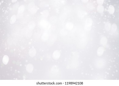 Silver  abstract bokeh background with snowflake and white glittering bokeh stars. A shiny holiday card. Glowing blurred lights