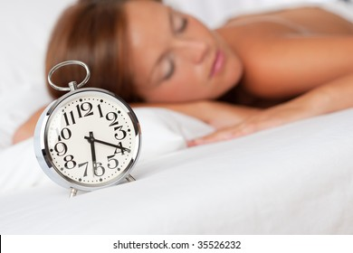 Silver alarm clock on white bed woman in background