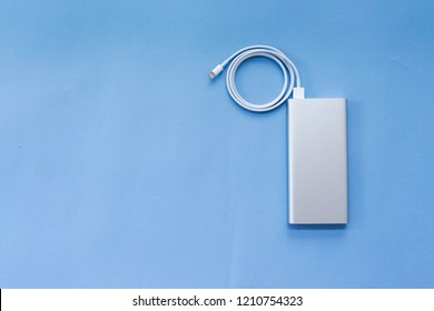Silver Aluminum Power Bank with USB Cable on Blue Background Top View