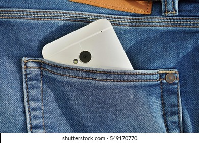 Silver aluminum smart phone placed at the stitched blue jean's back pocket