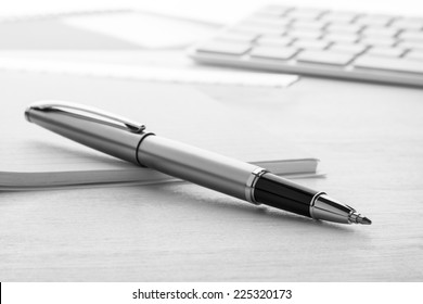 Silver ball pen with notebook on white desk.
