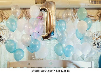 Silver balloon in form of number one surrounded with other blue balloons
