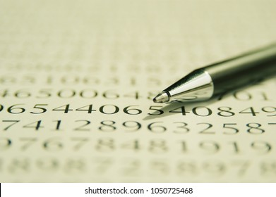 Silver ballpoint pen on a page of numbers, shallow depth of field shot with macro lens. Macro photography, close up of a pen laying on a sheet of numbers, finance and business concept.