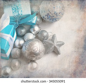 silver balls on the Christmas tree and Christmas presents in festive packaging with ribbons on a white wooden table. toned image, selective focus