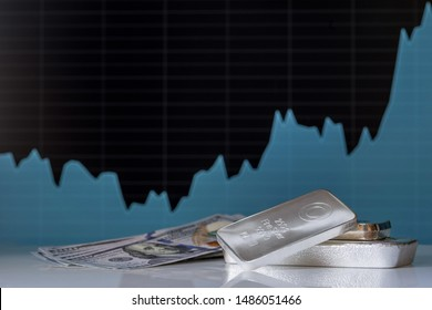 Silver bars and a hundred-dollar bills on the background of a growth chart. Selective focus.
