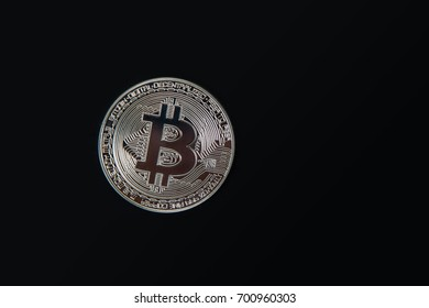 Silver Bitcoin coin on the black background