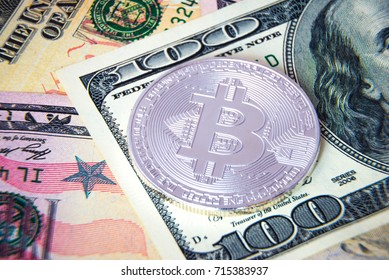 Silver bitcoin coin on US dollars; Financial concept; Closeup view