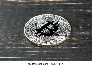 Silver bitcoin coin on wooden background, top view