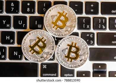 Silver bitcoin coins on the white keyboard. Close up. Bitcoin up.