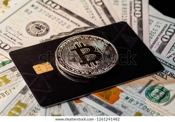 Silver bitcoin with credit card on top of dollars banknote background, new currency, accepting bitcoin for payment. Buy bitcoins online using credit or debit card concept.