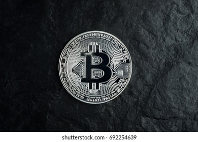 Silver bitcoin on black stone table background with texture, hard and solid, dark, isolated