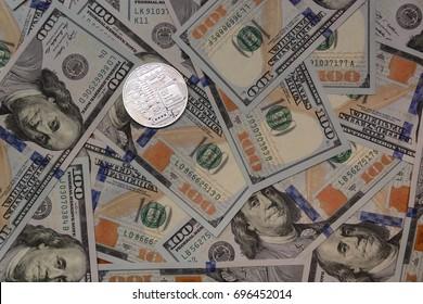 Silver bitcoin on hundred dollar bills