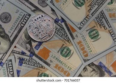 Silver bitcoin on hundred dollars bills