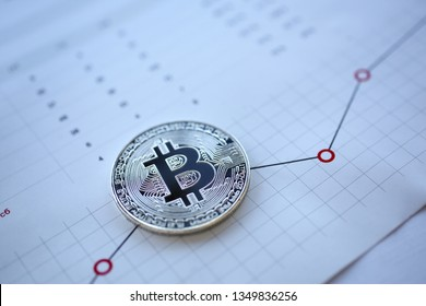 Silver bitcoin sign coin lying at stats graph paper closeup as idea of modern broker tool for success anti fraud buy and ambition education consultant career concept