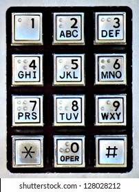 A silver and black keypad on a public payphone