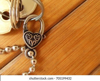 Silver and black miniature key chain lock in the shape of a heart on a bamboo wood bench