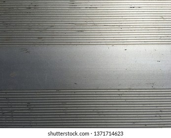 Silver bleacher seat surface with non slip serrated pattern.