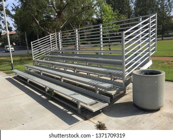 Silver bleachers and a cement trash can at Tustin Park from a corner angle.