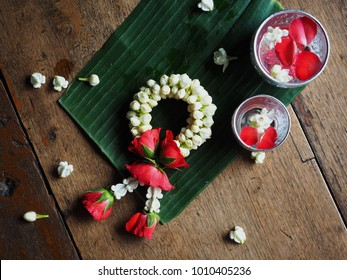 Silver blessing bowl of water, jasmine and rose petals and Garland of rose and jasmine on a banana leave with white crown flowers on wood for Thai culture and Thai Festival such as Songkran day.