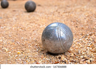 Silver bocce ball on gravel court with two darker bocce balls in the background