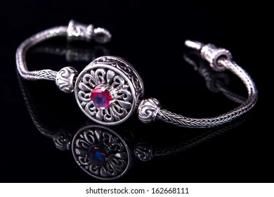 Silver bracelet with on black background.