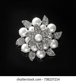 silver brooch flower with pearl isolated on black